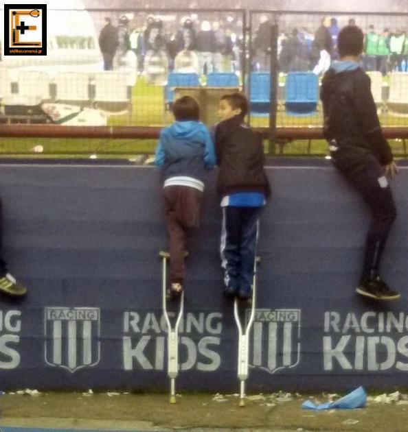 Δύο παιδιά πάνω σε πατερίτσες, βλέπουν αγώνα ποδοσφαίρου.