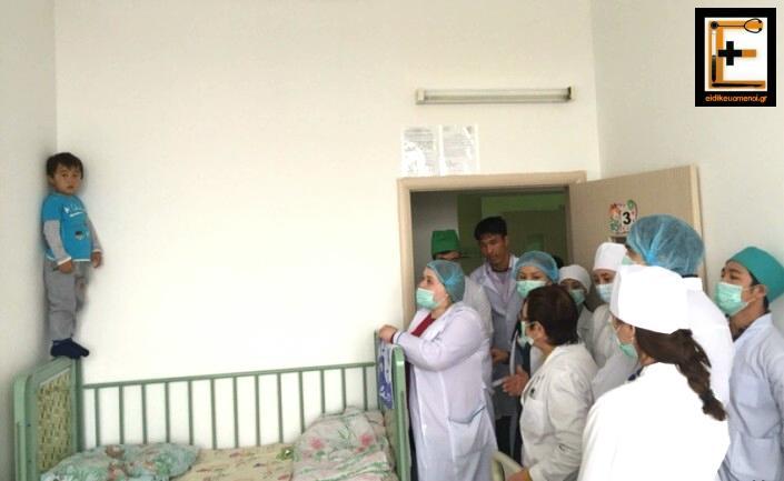 Παιδί όρθιο στο κρεβάτι φοβάται να κάνει ένεση μπροστά σε ιατρούς και νοσηλευτές. Παιδιατρικό παιδίατρος.